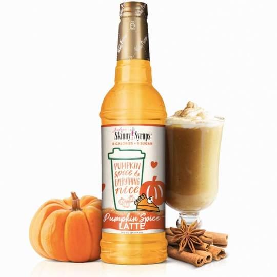 sugar free pumpkin spice latte syrup bottle next to mini pumpkin and latte