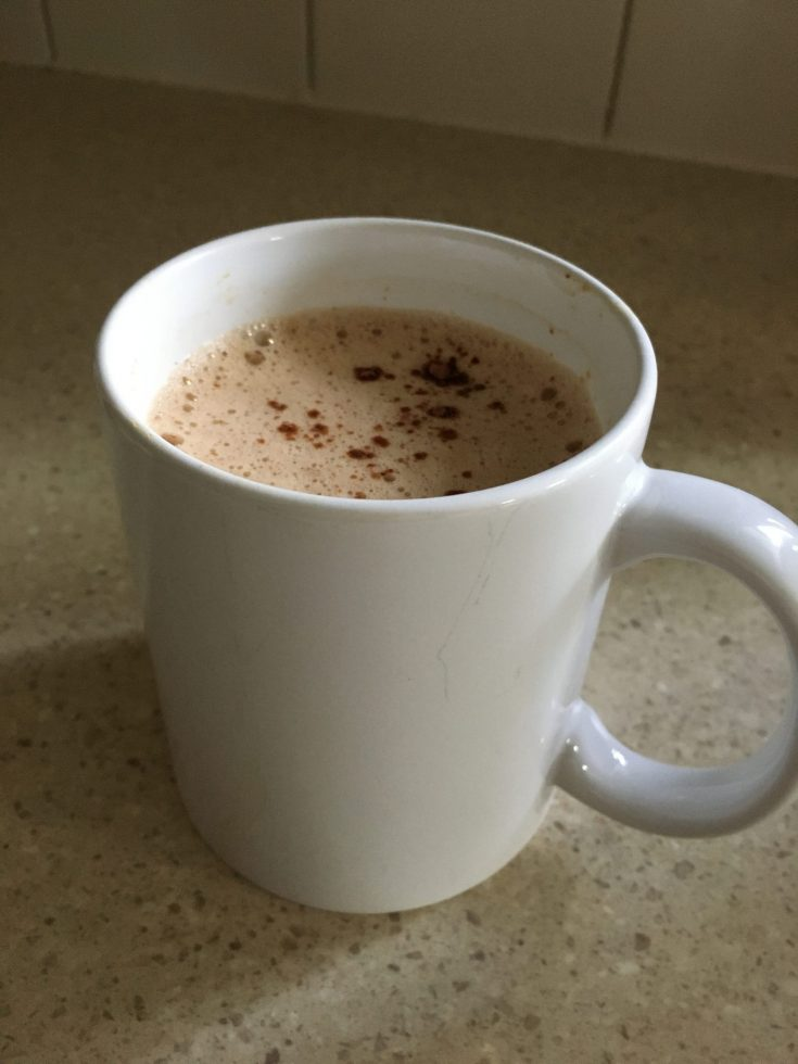Mug with frothy coffee and a sprinkle of cocoa on counter top. Sugar-free Keto peanut butter coffee recipe with Hershey's cocoa.