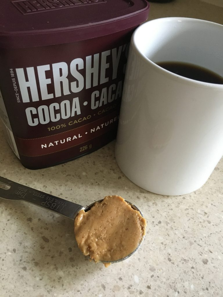 Hershey's Cocoa, mug with hot coffee, natural peanut butter in a measuring spoon on a counter top.  For the recipe keto peanut butter coffee