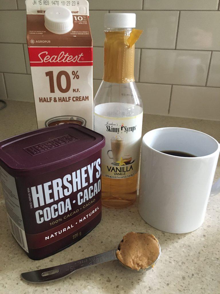 Cocoa, peanut butter, mug of coffee, vanilla, cream on a counter for sugar-free Keto vanilla peanut butter cup coffee recipe.