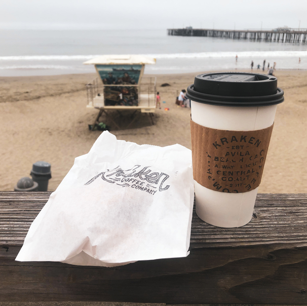 Image of disposable coffee mug and bag with desert inside sitting on picnic table with beach in the background.Best coffee in san luis obispo Kraken-Coffee-San-Luis-Obispo