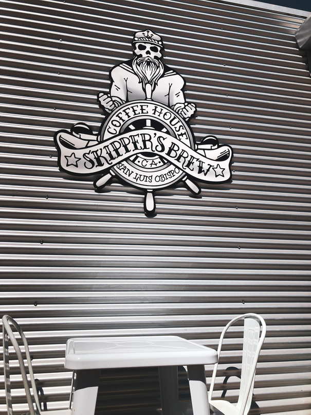 image of sign on wall above table and chairs. best coffee in san luis obispo Skippers-Coffee-San-Luis-Obispo (2)