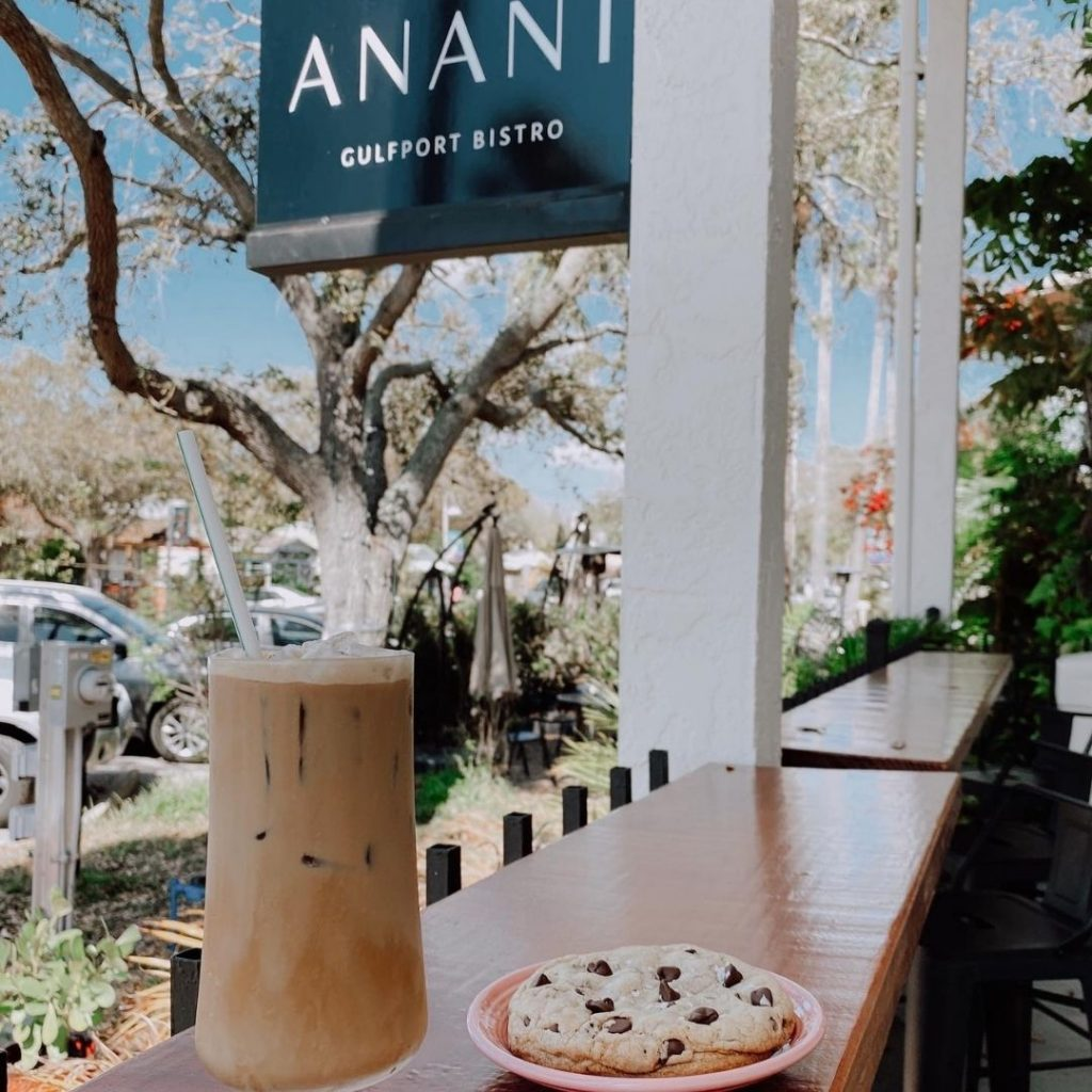 Glass of iced coffee sitting on table next to a chocolate chip cookie on an orange plate.  Backgroudn is Anani sign,white pillars, trees, and nature.  Best coffee shops in St. Pete.