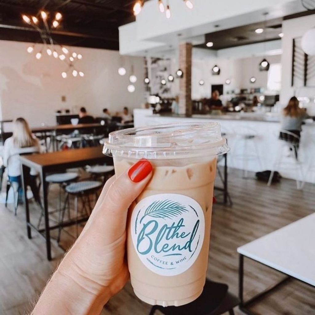 Hand holding iced coffee in plastic cup in front of scene of coffee shop with wood top tables, white counter, and soft modern lighting.  Best coffee shops in St. Pete.
