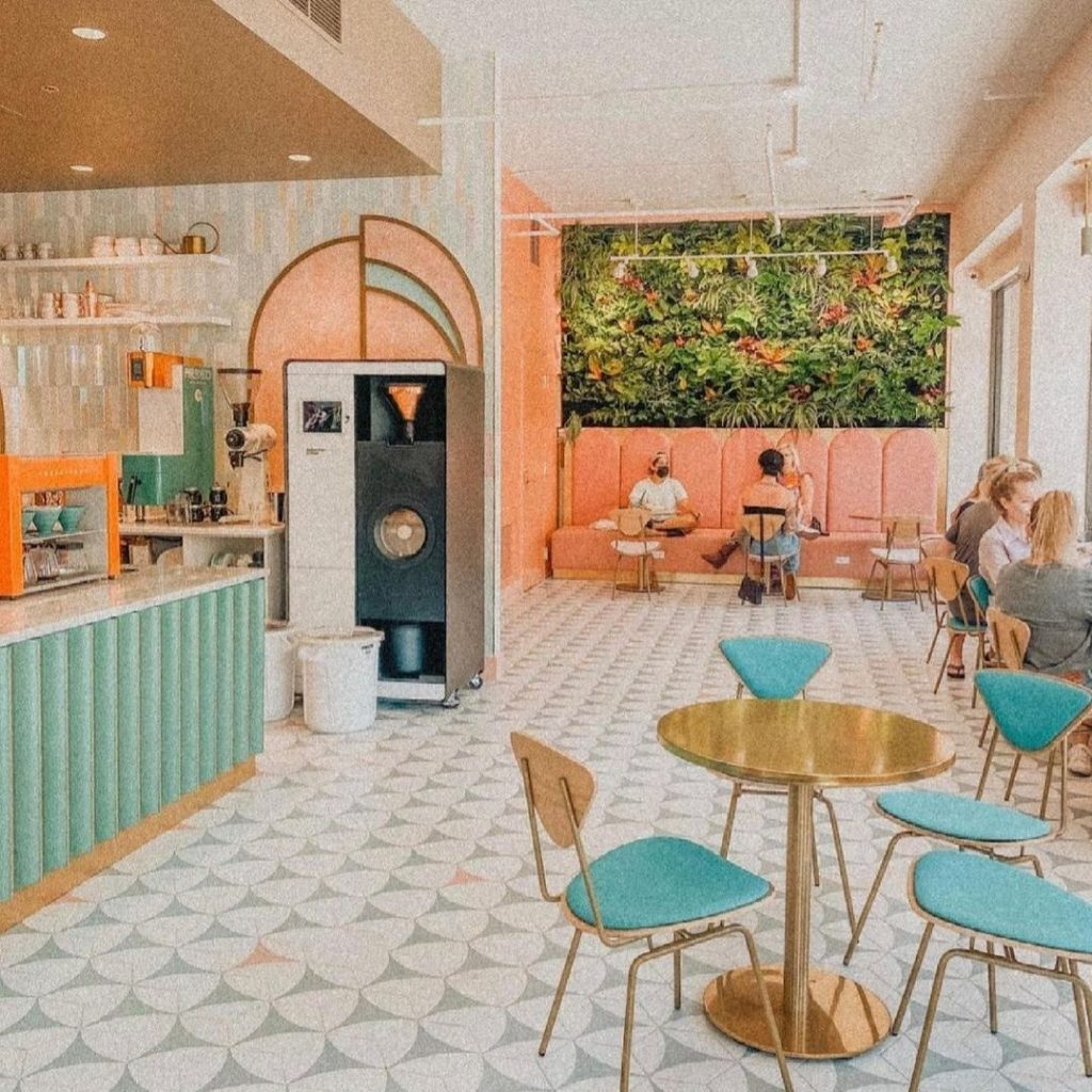 Coffee shop with gold table, teal covered chairs and counter, coral back wall with living wall.  People sitting in coffee shop.  Best coffee shops in St. Pete.