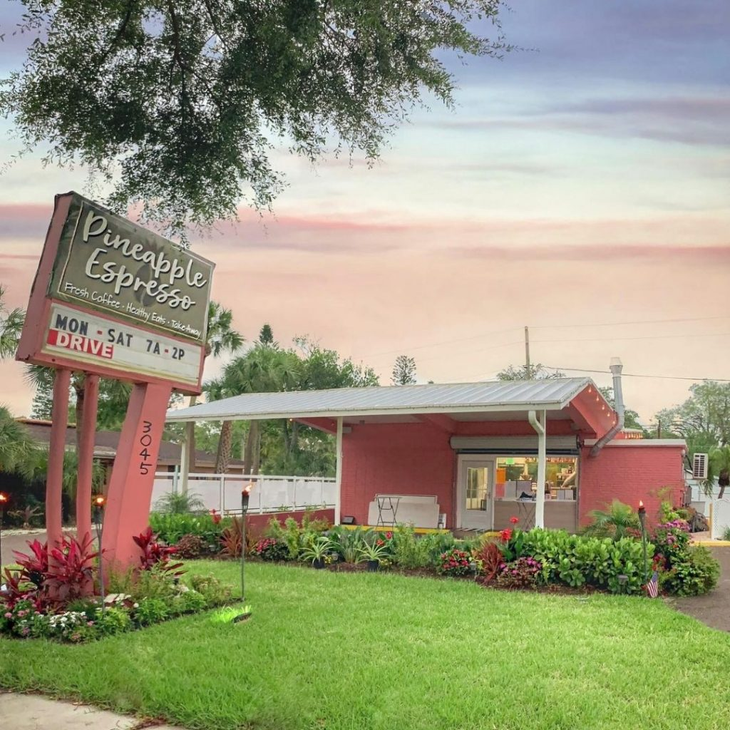 Front of Pineapple Espresso pink building, with sign, gardens, and the sun is setting, the sky is pink and blue.  Best coffee shops in St. Pete.